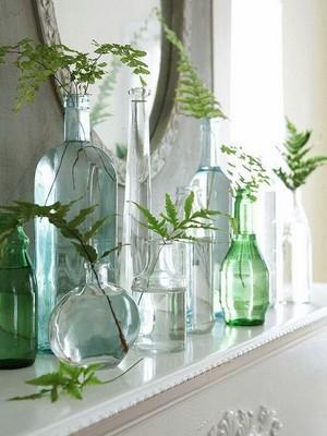 Bouteilles en verre et carafes transparentes utilisées en soliflores avec des feuilles de fougères