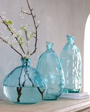Branche de fruitier en fleur dans un vase bleu transparent