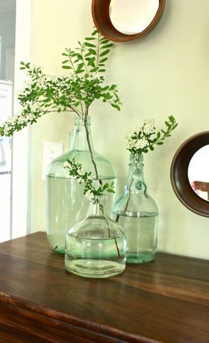 Branches et fleurs dans des carafes et bouteilles en verre