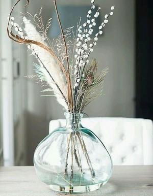 Bouquet de fleurs séchées et fraîches mélangées dans un vase bleu transparent