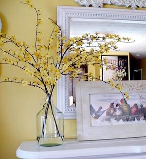 Branches et fleurs de forsythia dans une bouteille en verre ou bonbonne transparente