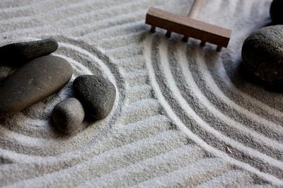 jardin zen sec avec du sable, des galets et un rateau