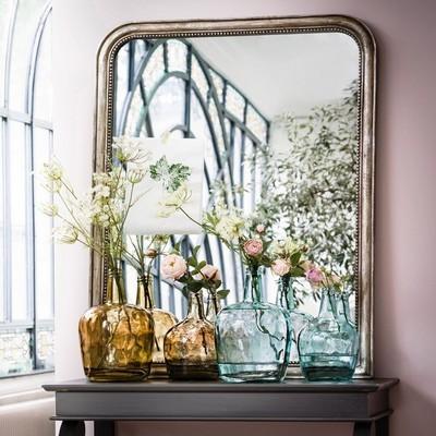 Dame jeanne vases marron et bleu contenant des fleurs roses devant un grand miroir