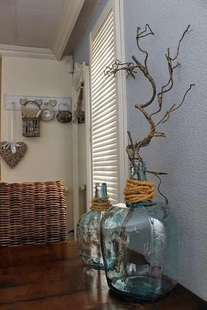Branches de bois décoratives dans une dame jeanne bleue