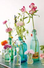 Bouteilles en verre transparentes vertes et bleues utilisées comme soliflore avec des fleurs variées et colorées