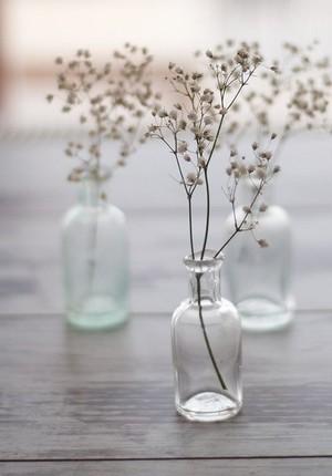 Petites fleurs blanches fines dans une bouteille en verre transparent pour un bouquet aérien