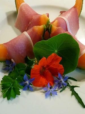 Recette de fleurs comestibles: bourrache bleue, capucine orange avec du jambon de parme et du melon. En savoir plus: lisez l'article sur le blog.