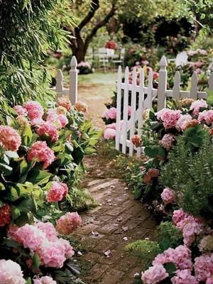 Allée de jardin à l'anglaise, pavée pour plus de praticité. Découvrez l'article du blog sur les styles de jardin anglais.