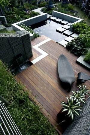 Jardin moderne de style exotique et tropical, avec son bassin et sa terrasse en teck. Pour en savoir plus sur les jardins modernes, lisez l'article du blog!